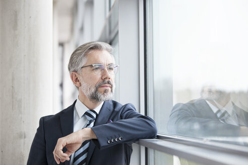 Thoughtful businessman looking out of window - RBF002554