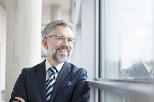 Confident businessman looking out of window - RBF002556