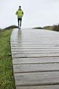 Spain, Valdovino, defocused man running on a boardwalk at a rainy day - RAEF000086