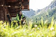 Austria, Altenmarkt-Zauchensee, young woman with dog at alpine cabin - HHF005175