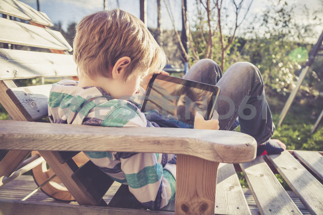 Boy playing with digital tablet on wooden deckchair - SARF001567