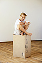 Happy boy sitting on cardboard box in an empty room showing thumb up - LBF001087