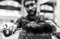 Hairdresser cutting young man's hair in a  barbershop - MGOF000141