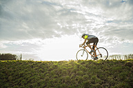 Germany, Mannheim, young man riding bicycle - UUF003633