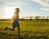 Germany, Mannheim, young man jogging in meadow - UUF003638
