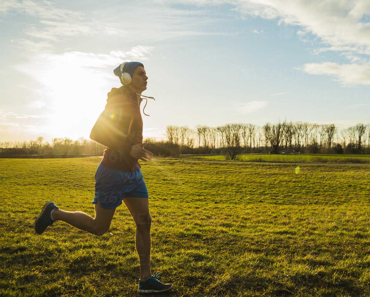 Germany, Mannheim, young man jogging in meadow - UUF003638 - Uwe Umstätter/Westend61