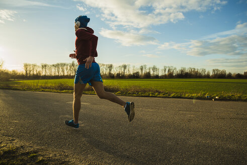 Germany, Mannheim, young man jogging on rural road - UUF003639