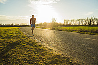 Germany, Mannheim, young man jogging on rural road - UUF003640