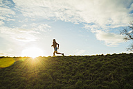 Germany, Mannheim, young man jogging at sunrise - UUF003642