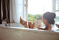 Woman relaxing in bathtub reading book - MBEF001335