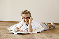 Portrait of smiling boy lying on wooden floor with a book - LBF001098