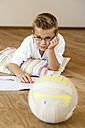 Boy doing homework on wooden floor looking at soccer ball - LBF001095