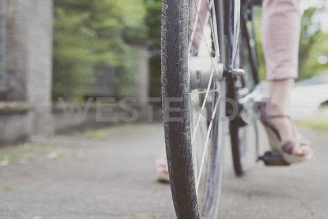 Close-up of woman with wedges on bicycle - CHPF000113