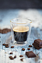 Glass cup of espresso, roasted coffee beans and dark chocolate on wood - LSF000011