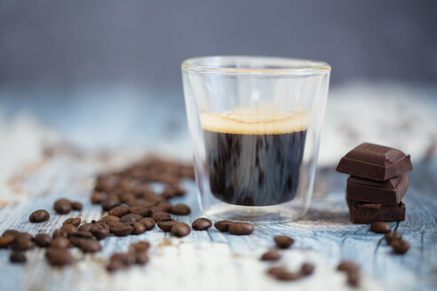 Glass cup of espresso, roasted coffee beans and dark chocolate on wood - LSF000012