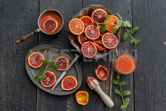 Sliced blood oranges and glass of blood orange juice on wood - SARF001535