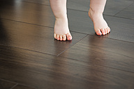 Feet of baby girl on dark floor - JTLF000086