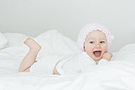 Laughing baby girl with cap lying on bed - JTLF000099