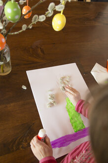 Girl working on Easter painting with glue stick - SARF001550