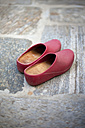 Pair of red rubber gardening shoes on stone floor - LSF000026