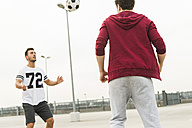 Two young men playing soccer on parking level - UUF003678