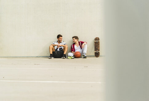 Two young men sitting with skateboard and basketball on parking level - UUF003684