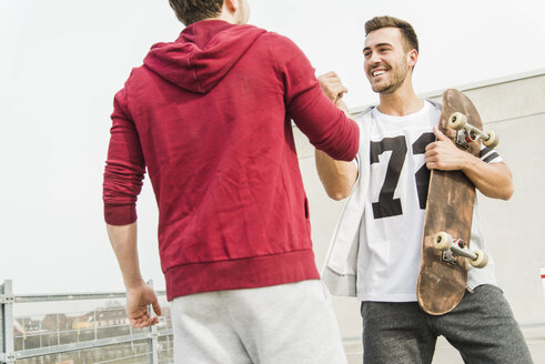Young man with skateboard shaking hands with friend outdoors - UUF003691