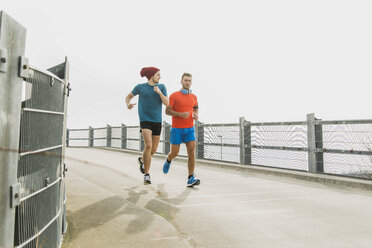 Two young men jogging on bridge - UUF003705