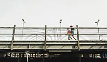 Two young men jogging on bridge - UUF003706