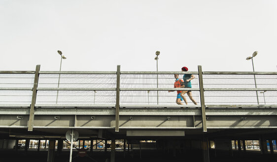 Two young men jogging on bridge - UUF003706