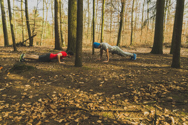 Two young men doing push-ups in forest - UUF003714