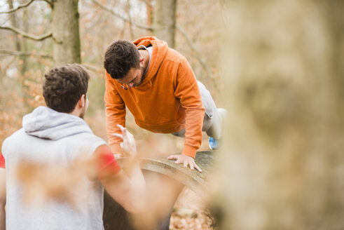 Two young men exercising in forest - UUF003723