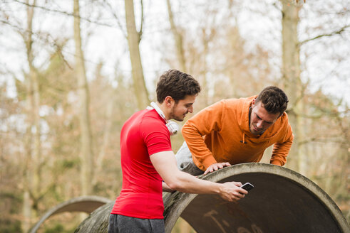 Two young men exercising in forest - UUF003726