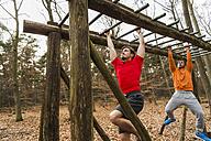 Two young men brachiating on climbing frame - UUF003729