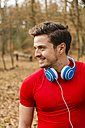 Smiling young man with headphones in forest - UUF003740