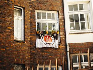 Germany, Hamburg, flag of FC St. Pauli hanging on house facade - KRP001395