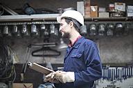 Warehouseman in storehouse holding clipboard - SGF001405