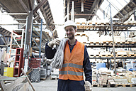Smiling warehouseman in storehouse carrying tubes - SGF001420