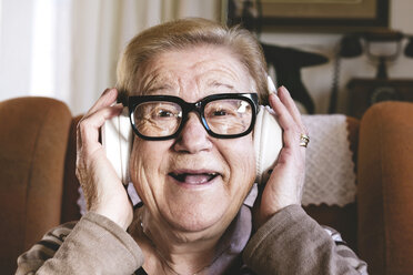 Portrait of happy elderly lady hearing music with headphones - GEMF000140