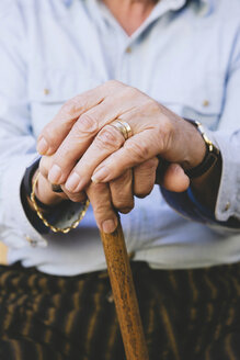Close-up of old man's hands resting on a cane - GEMF000142