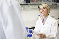 Smiling scientist in laboratory talking - RBF002602
