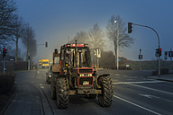 Germany, Grevenbroich, tractor and car driving through a red light on a crossroad - FR000226