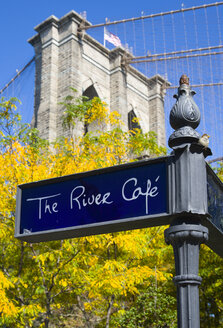 USA, New York, Brooklyn Bridge Park, signpost for The River cafe and detail of one of the suspension bridge towers - PS000670