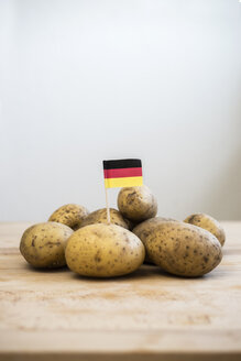 Row potatoes and small german little flag on wood - CHPF000122