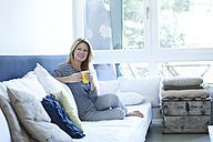 Relaxed woman sitting on couch with cup of coffee - MAEF009961