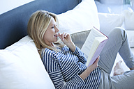Woman reading book on a couch - MAEF009986