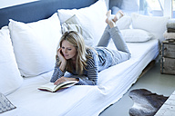 Woman lying on couch reading a book - MAEF009977