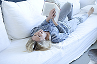 Woman lying on couch reading a book - MAEF009982