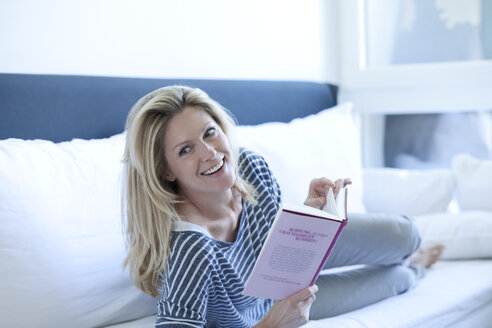 Portrait of smiling woman lying on couch with a book - MAEF009984