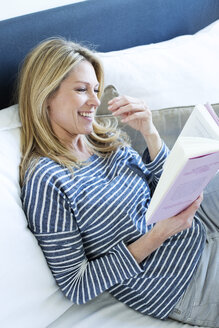 Woman sitting on couch reading a book - MAEF009988